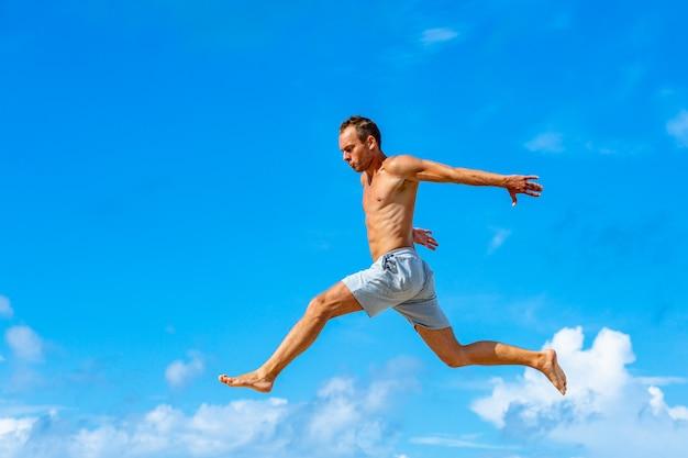 日当たりの良い夏の日に青空の背景にパルクールジャンプを行う若い男
