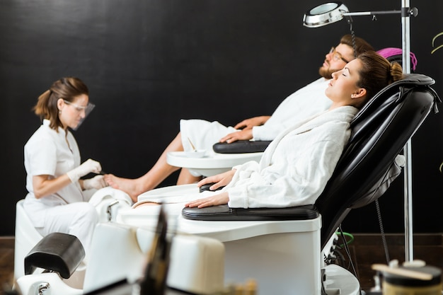Young man doing pedicure in salon. beauty concept.