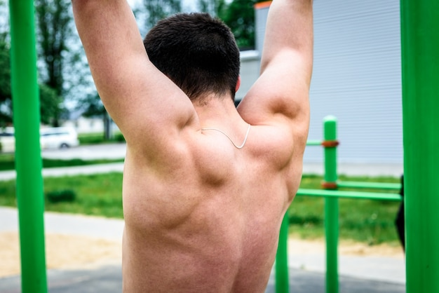 Young man doing pull ups on horizontal bar outdoors on sports playground. street workout.