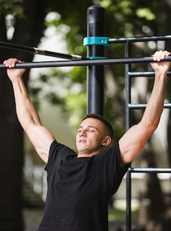 Young man doing pull ups on horizontal bar outdoors, workout, sport concept.