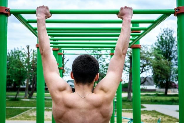 Молодой человек делает подтягивания на турнике на открытом воздухе на спортивной площадке. уличные тренировки.