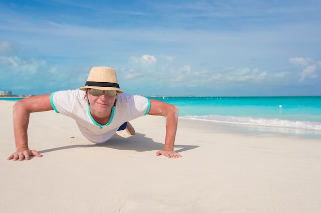 Young man doing push ups on perfect beach