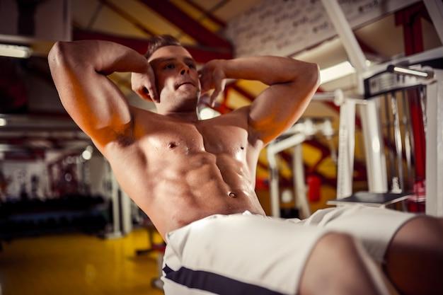 腹筋運動をしている若い男のジムでベンチプレス