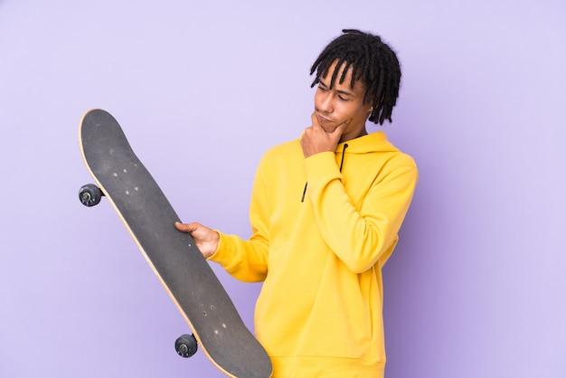 Young man doing skate over isolated wall