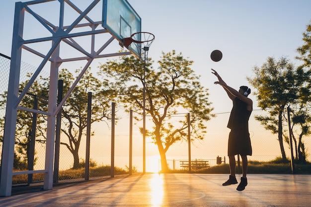 Молодой человек занимается спортом, играет в баскетбол на рассвете
