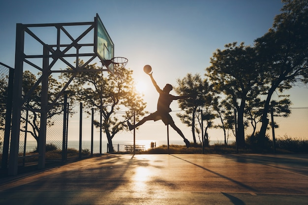 Young man doing sports, playing basketball on sunrise, jumping silhouette
