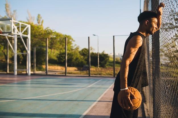 Young man doing sports, playing basketball on sunrise Free Photo