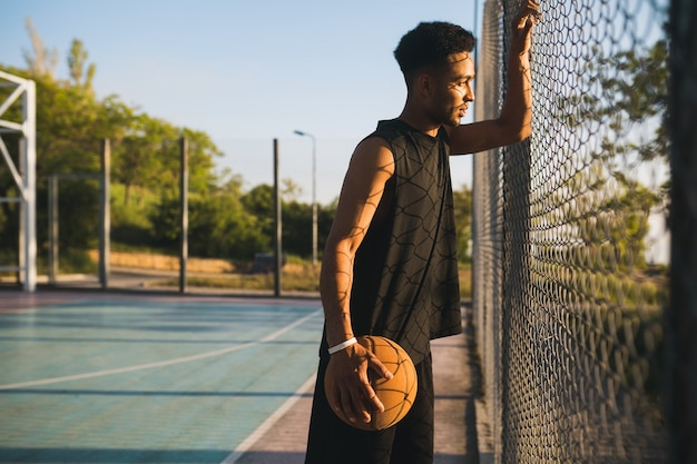 Young man doing sports, playing basketball on sunrise