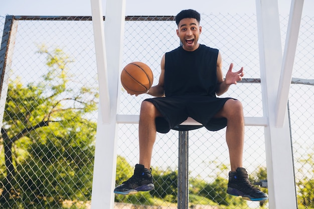 Young man doing sports, playing basketball