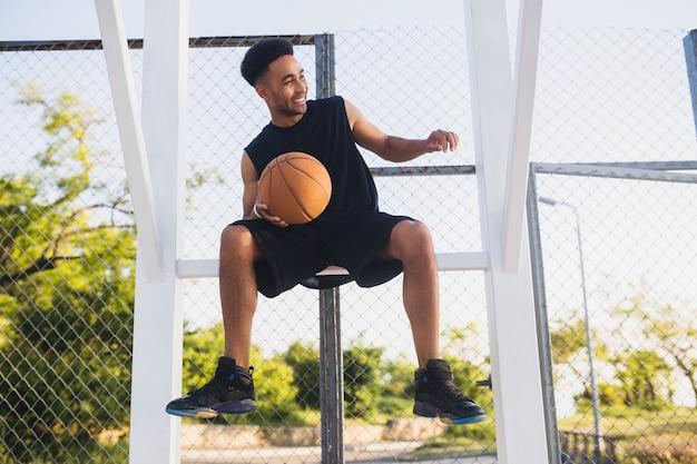Молодой человек занимается спортом, играет в баскетбол
