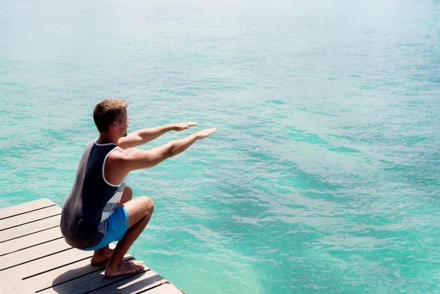 若い男が海でスクワットをします。休暇中に運動する朝。