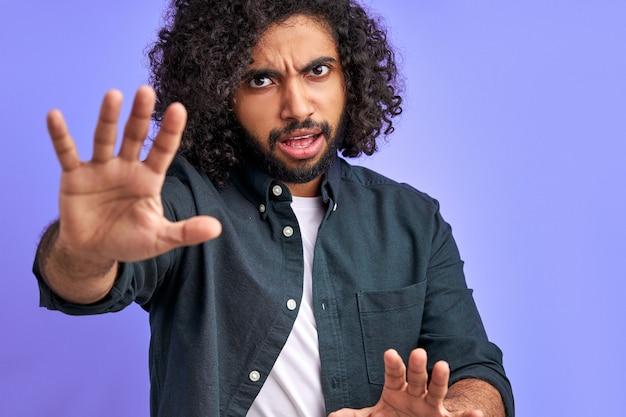 手のひらで一時停止の標識をしている若い男、紫色の空間で隔離された顔に否定的で深刻なジェスチャーで警告表現