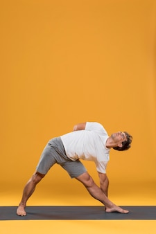 Young man doing stretching exercise on yoga mat