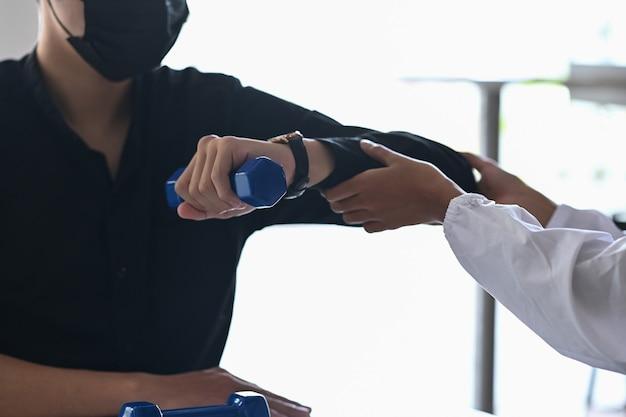 의료 클리닉에서 물리 치료사와 함께 치료를 하는 젊은 남자.