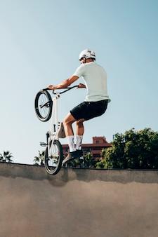 Молодой человек делает трюки на своем велосипеде