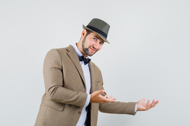 Young man doing welcome gesture politely in suit, hat and looking gentle , front view.
