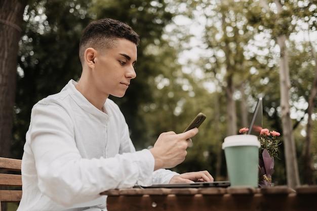 공원에서 원격으로 일을 하는 젊은 남자. 밖에서 일하는 프리랜서.