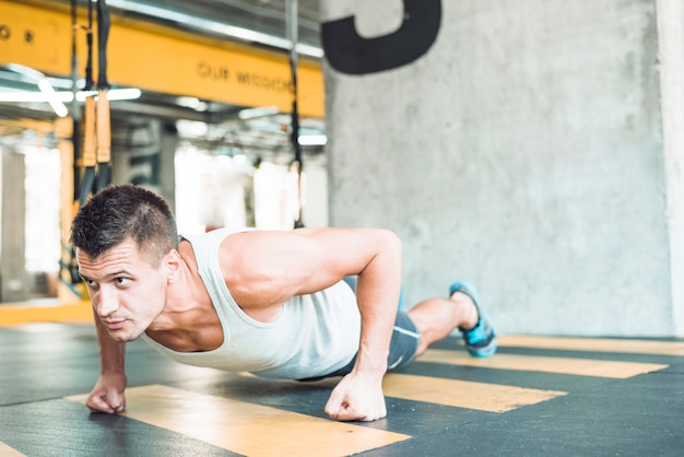 Young man doing workout in fitness club
