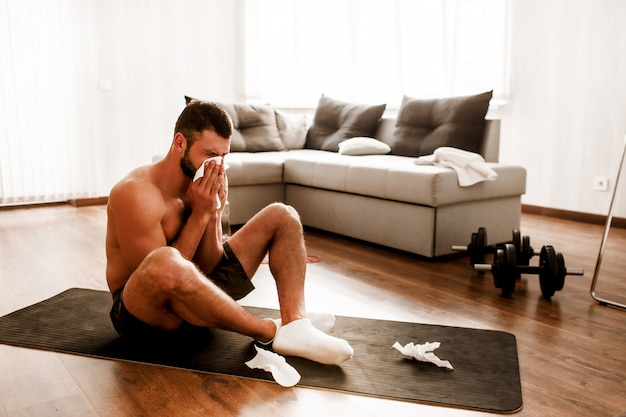 Young man doing yoga workout in the room .
