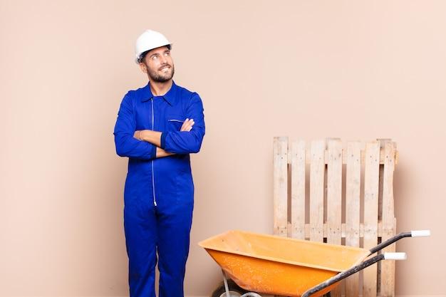 젊은 남자가 의심하거나 생각하고, 입술을 물고 불안하고 긴장된 느낌, 측면 건설 개념에 공간을 복사하려고합니다.