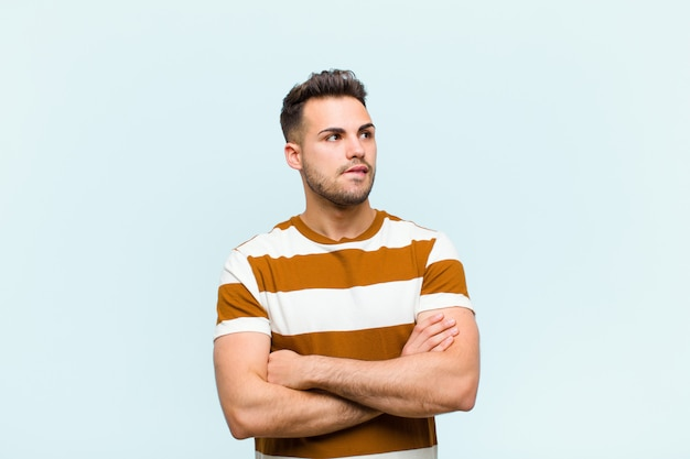 Young man doubting or thinking, biting lip and feeling insecure and nervous, looking to copy space on the side over blue wall