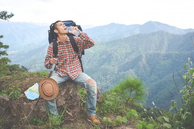Молодой человек пил воду на вершине холма в тропическом лесу вместе с рюкзаками в джунглях. приключения, походы