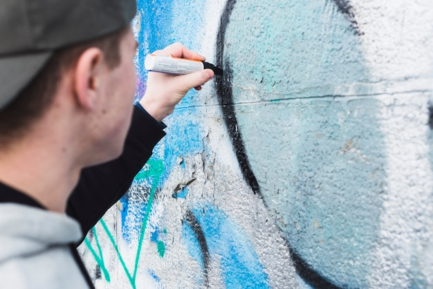 Young man drawing graffiti on street wall