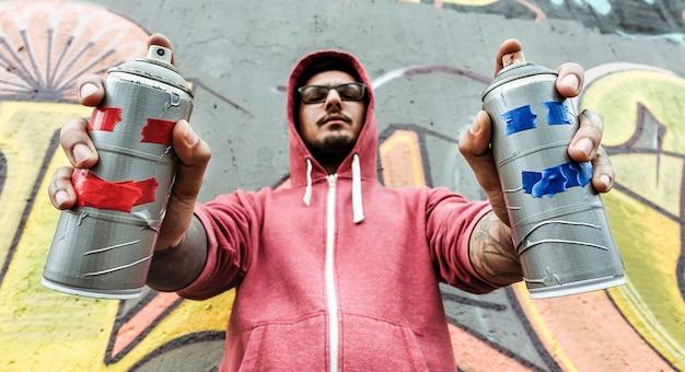 Молодой человек, рисование спреями. граффити-художник рисует аэрозольными баллончиками на стене