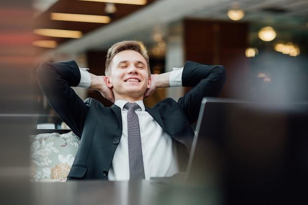 Молодой человек мечтает об отпуске, расслабляется после тяжелого рабочего дня после ноутбука в кафе