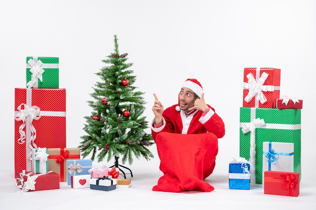 Young man dressed as santa claus with gifts and decorated christmas tree sitting in the ground making call me gesture and pointing above