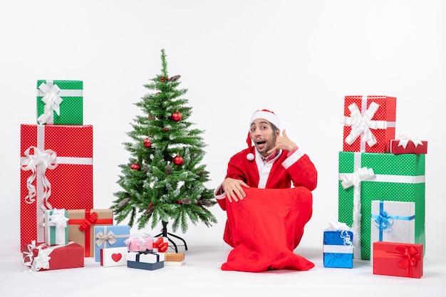 Giovane uomo vestito da babbo natale con doni e albero di natale decorato seduto per terra e facendo gesto di chiamata