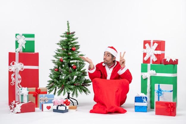 Giovane uomo vestito da babbo natale con doni e albero di natale decorato seduto per terra facendo gesto di vittoria che indica qualcosa