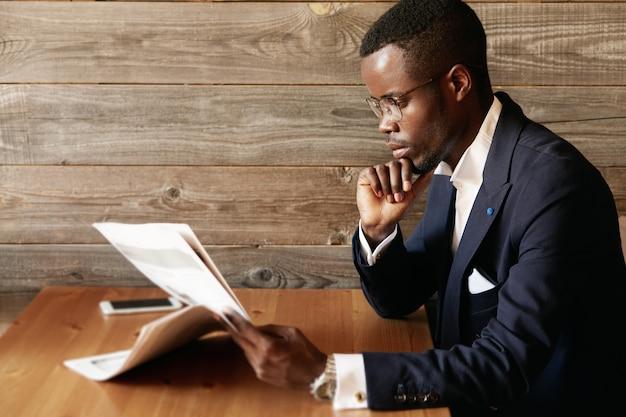 Giovane uomo vestito in abito formale seduto nella caffetteria
