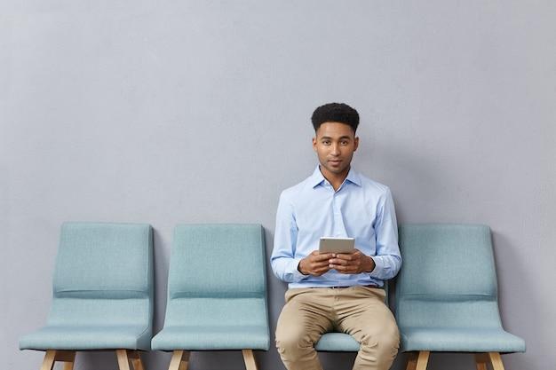待合室に正式に座っている服を着た若い男