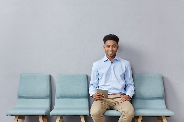 젊은 남자가 공식적으로 대기실에 앉아 옷을 입고