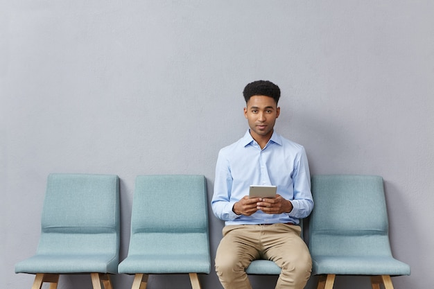 Young man dressed formally sitting in waiting room