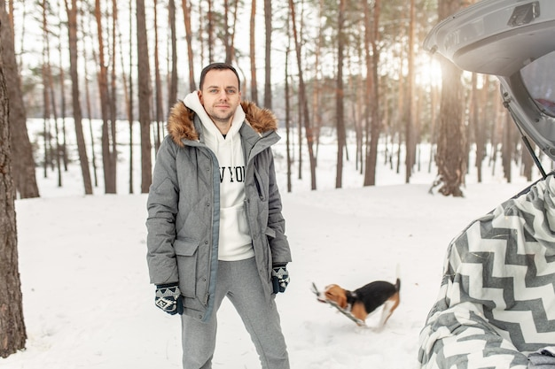 A young man dressed in a gray winter park in a snowy winter forest with beagle.