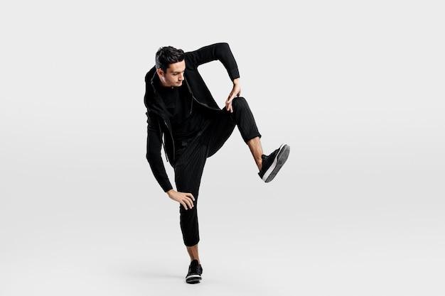 スタイリッシュな黒い服を着た若い男がストリートダンスを踊りながら片足を持ち上げる
