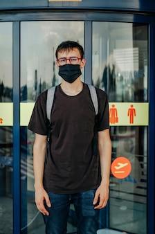 Молодой человек в черной футболке, джинсах, хирургической маске, очках и рюкзаке стоит перед дверями аэропорта и смотрит в камеру