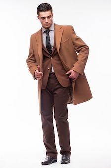 白い壁に隔離されたコートを着た若い男