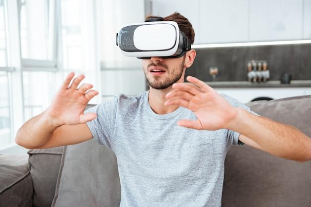 Молодой человек, одетый в серую футболку, носящий устройство виртуальной реальности, сидя на диване