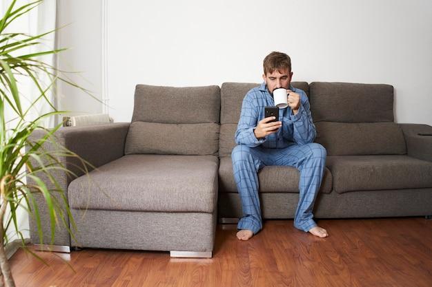 젊은 남자가 집에서 잠옷을 입고 스마트 폰을 확인하는 동안 소파에 앉아 커피를 마시고 있습니다.