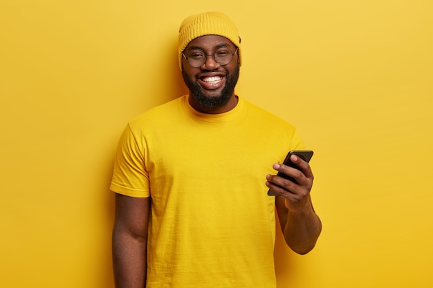 Молодой человек, одетый в желтый, держа телефон