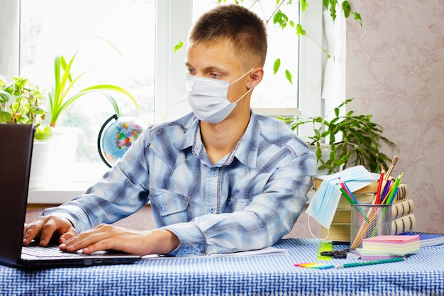 A young man, dressed in a plaid shirt and a sterile mask, sits at a table and looks at a laptop . education concept. poor epidemiological situation.