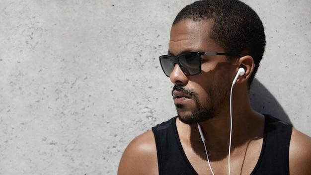 Giovane uomo vestito in abiti sportivi che ascolta la musica