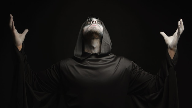 若い男は、黒い背景の上のハロウィーンの闇の天使に扮した。