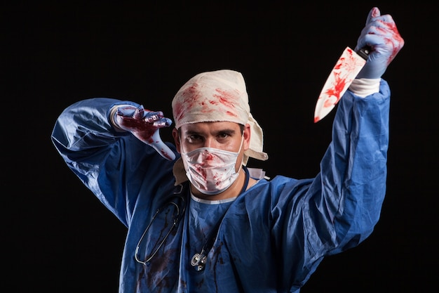 Young man dressed up like a doctor with schizophrenia for halloween carnival. maniac doctor with knife covered in blood.