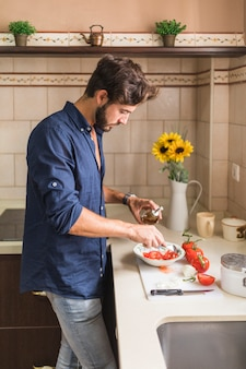 Young man dressing the salad with olive oil in the kitchen