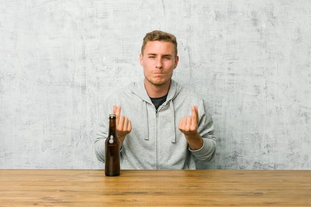 Молодой человек пьет пиво на столе, показывая, что у нее нет денег.