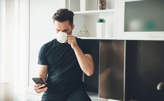 검은 옷을 입고 모바일 채팅하는 동안 부엌에서 커피를 마시는 젊은 남자
